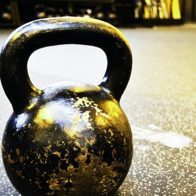 A lone kettlebell sitting on a gym floor